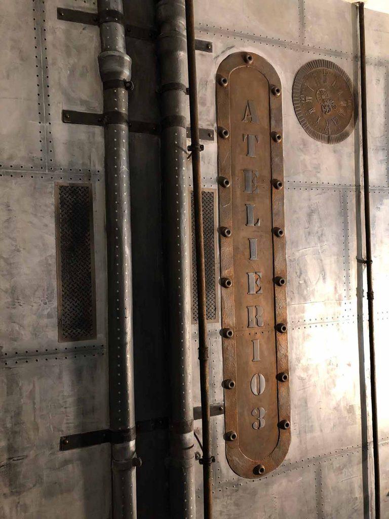 décoration industrielle appartement avec murs métal et enseigne publicitaire style industrielle