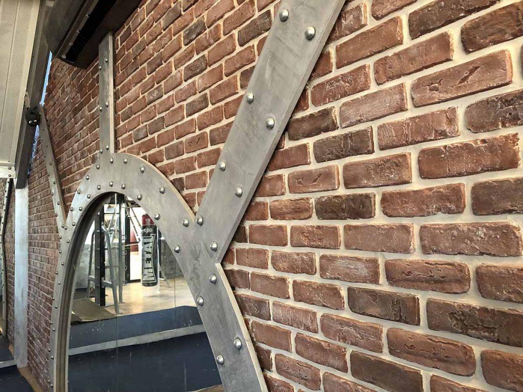 salon de coiffure style industriel avec mur de briques et arche métallisée.